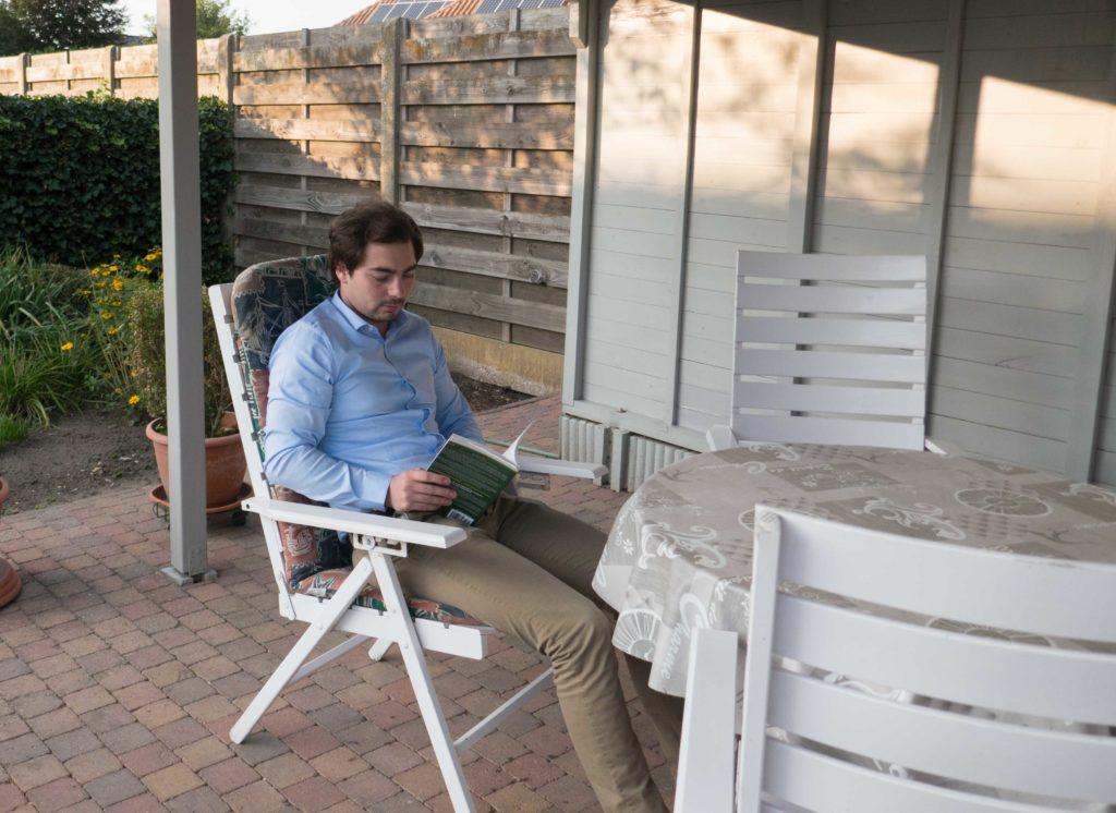 Stef leest een boek op het tuinterrras