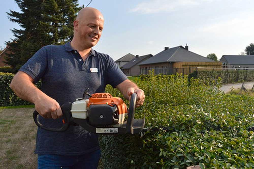 Guy scheert de haag in z'n tuin.